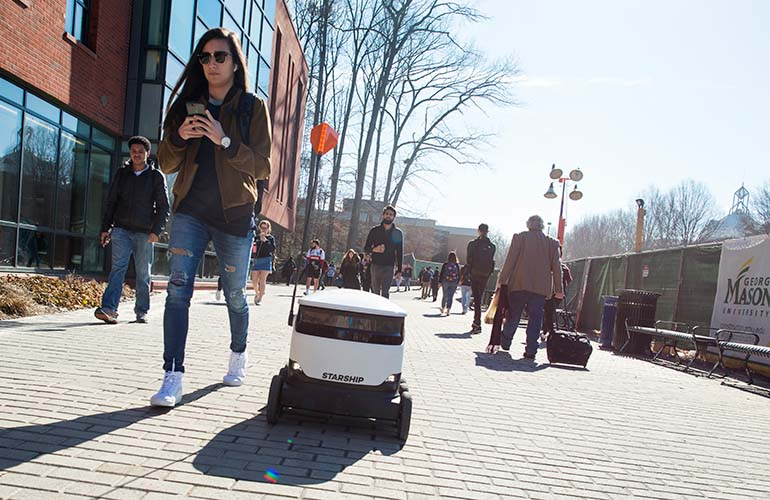 a starship delivery pod moves through a crowd of students