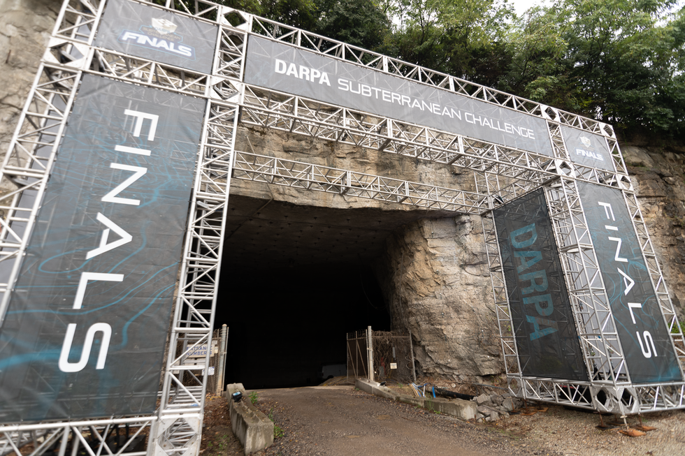 A scaffolding with DARPA banners outside of the entrance to a cave