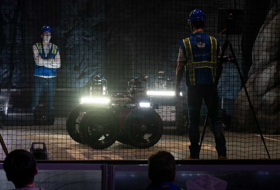 Two roboticists watching three large wheeled robots with bright lights