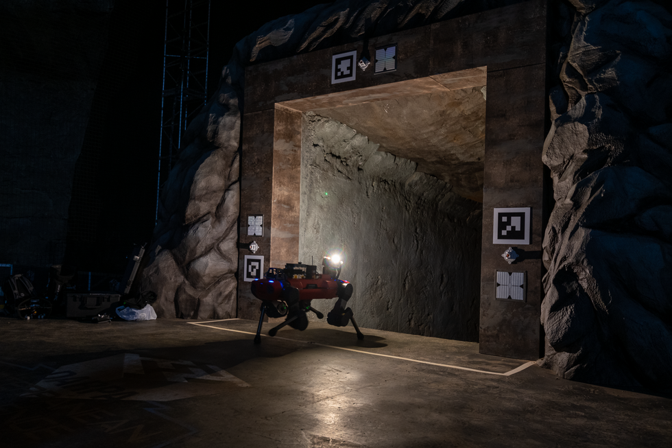 A red quadrupedal robot with a bright light walks into a dark cave entrance