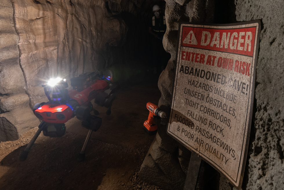 """A red quadrupedal robot in a cave walks past a drill on a wall and a sign that says """"danger enter at your own risk"""""""