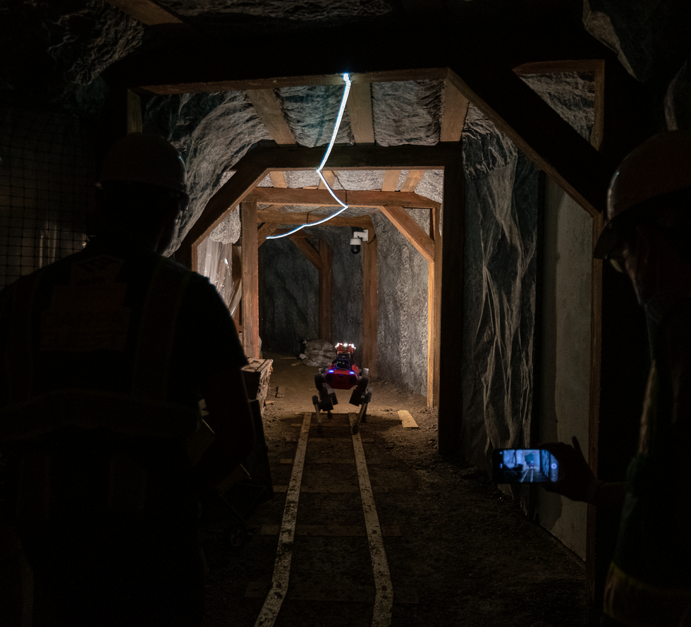 A red quadrupedal robot walks down a mine tunnel as two roboticists look on