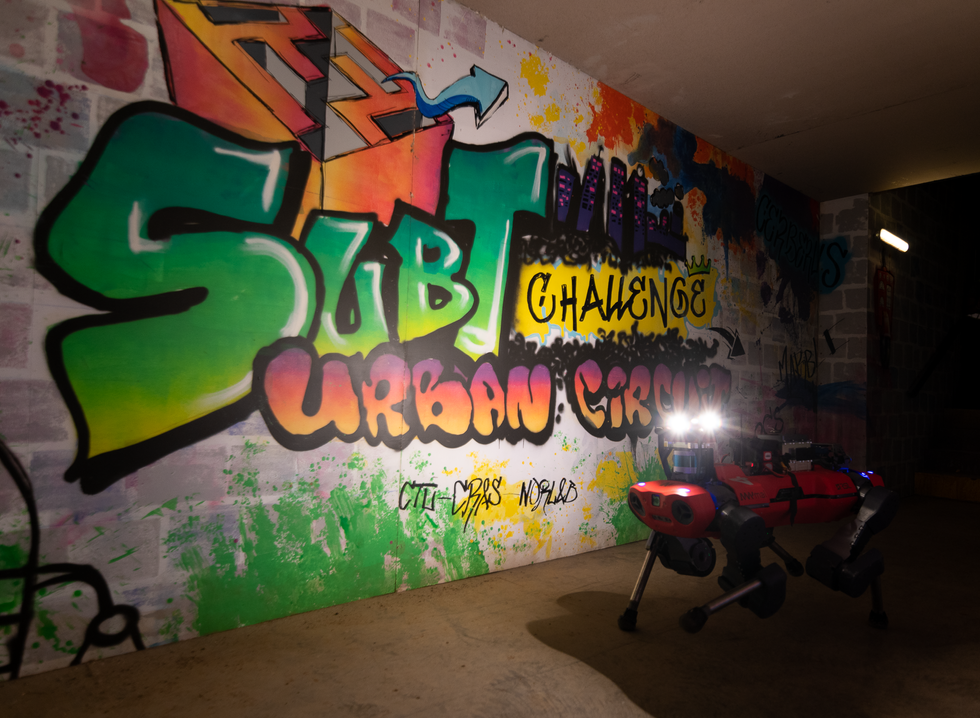 """A red quadrupedal robot walks past a wall of brightly colored graffiti that reads """"SubT Urban Circuit"""""""