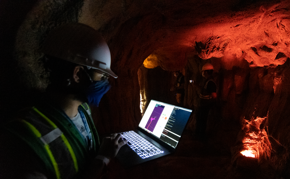 A roboticist looks at data on a laptop in a cave lit with a red light