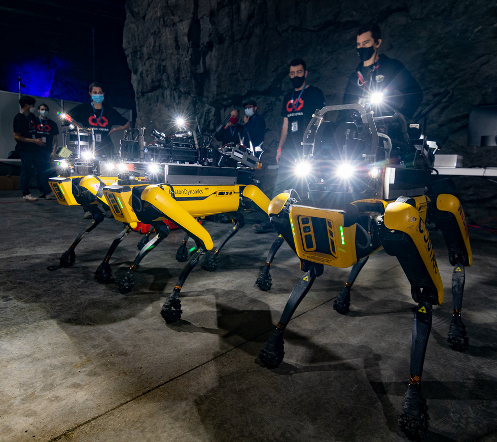 Four yellow quadrupedal robots standing with a group of humans