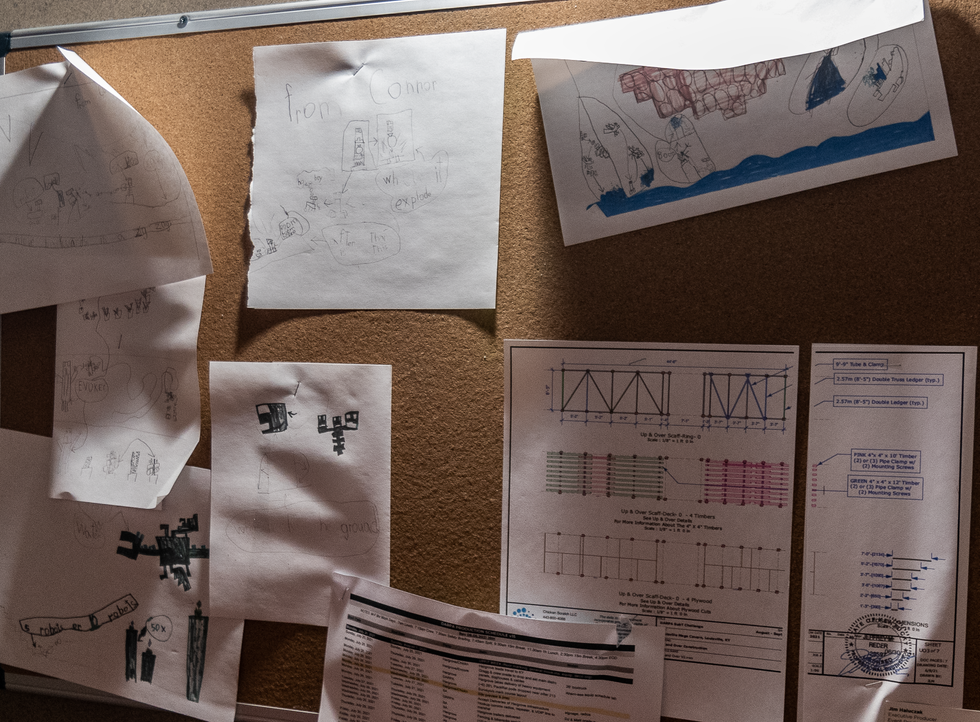 A cork board with papers stapled to it showing drawings of Minecraft monsters
