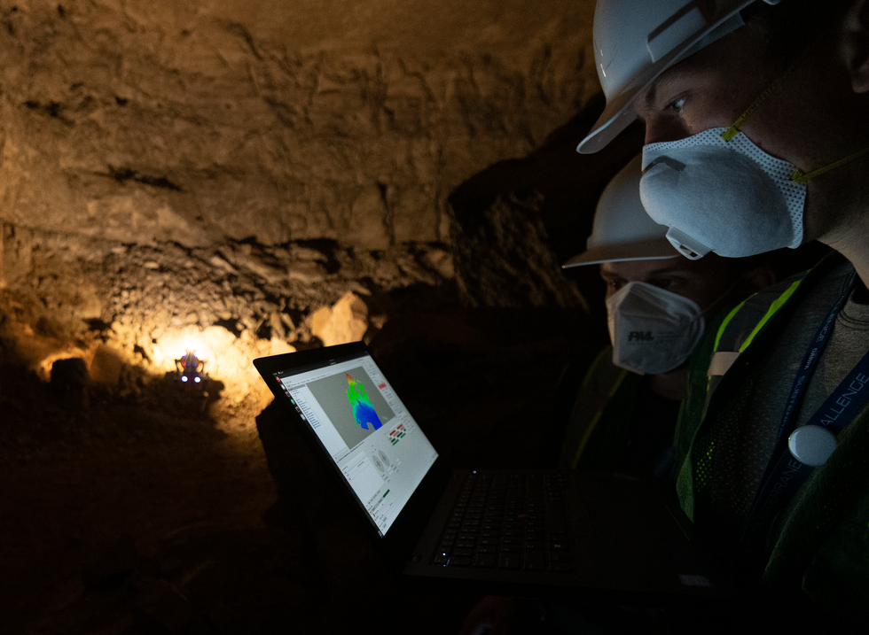 Two roboticists look at data on a laptop as a quadrupedal robot lights up a cave in the background