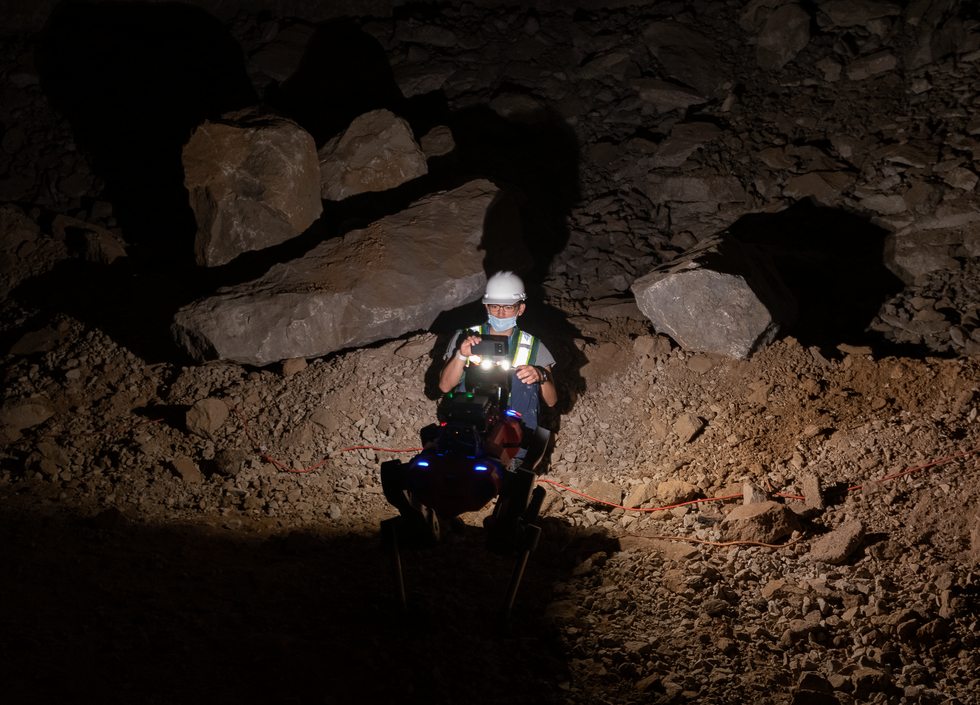 A red quadrupedal robot stands directly in front of a crouching human recording it with a cell phone in a dark cave