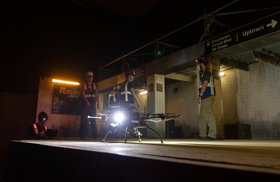 A drone with a bright light sits on a dark subway platform with a group of roboticists behind