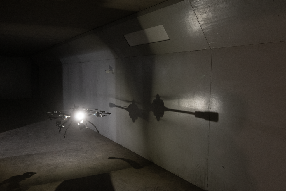 A drone with a bright light hovers in a long hallway with white walls