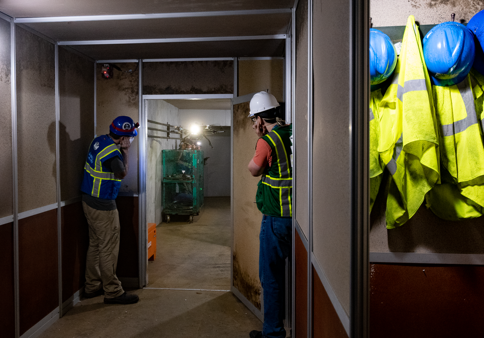 Two roboticists covering their ears watch a drone through a doorway next to a closet with yellow safety vests and blue helmets hanging on pegs