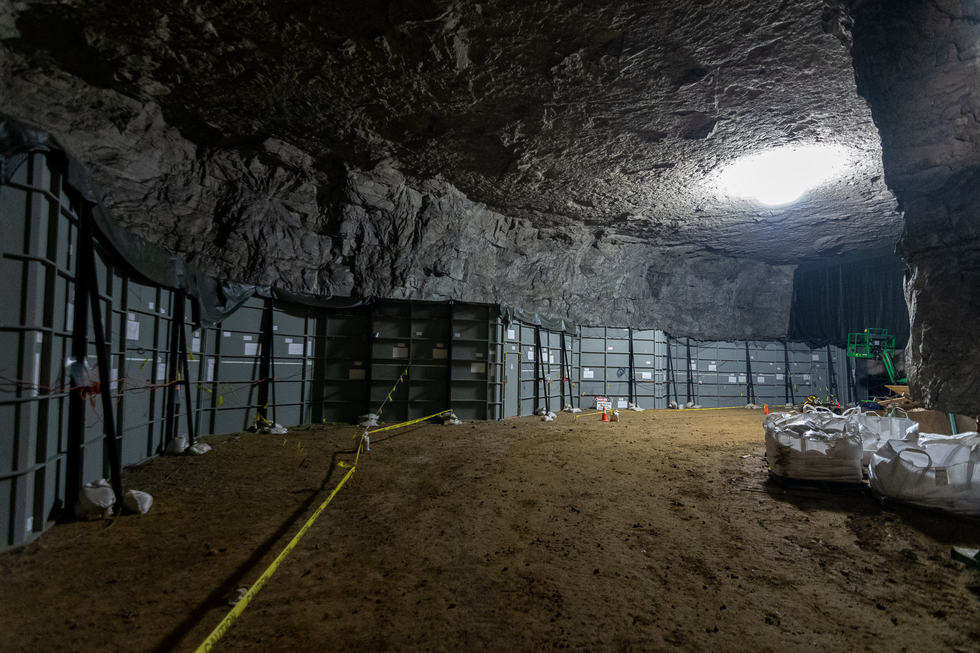 Inside of a large cave a tunnel made of shipping containers stretches along one wall