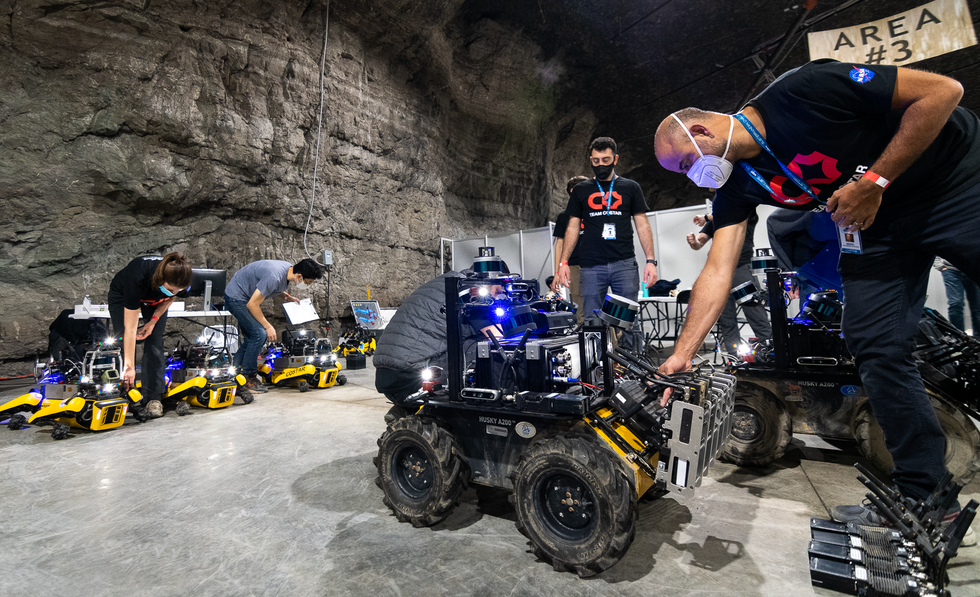 Roboticists in a cave adjusting electronics on wheeled and legged robots
