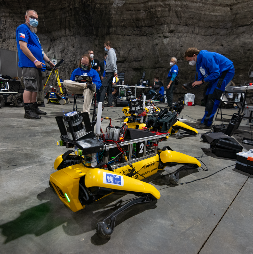 Two yellow quadrupedal robots lying down with roboticists in the background