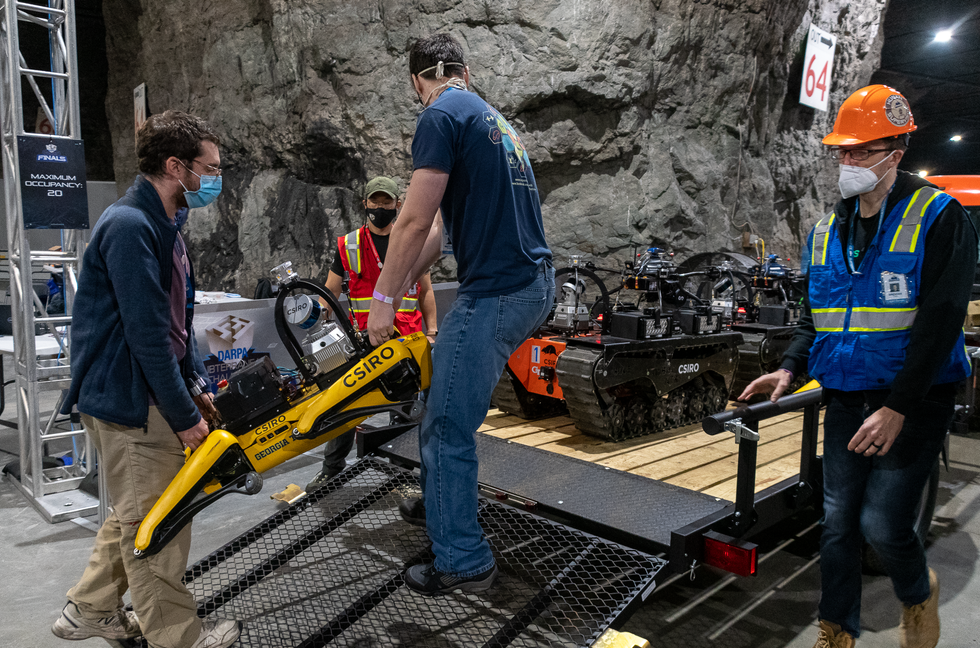 Roboticists carry a yellow legged robot up a ramp onto the back of a trailer