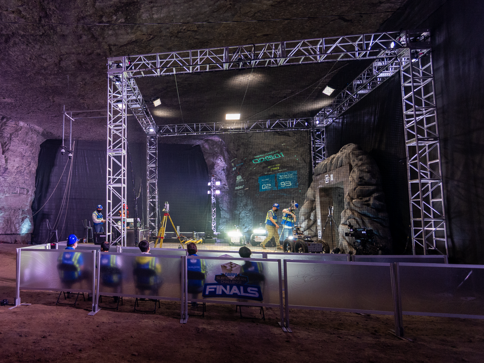 A large cave with a stage and a stone portal on one side, dramatically lit