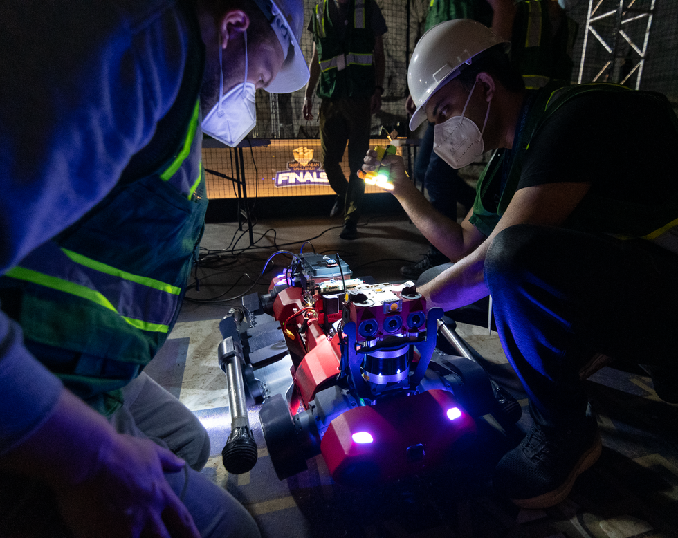 Two roboticists crouch over a red quadrupedal robot in the dark, one holds a flashlight
